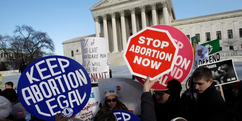 March for Life participants and counter-protesters hold signs in front of the U.S. Supreme Court in Washington. A survey released April 17 by the Public Religion Research Institute shows that despite abortion being part of the national debate for nearly half a century, Americans still consider it a complicated issue. (CNS photo/Peter Lockley) See ABORTION-ATTITUDES-POLL April 17, 2018.