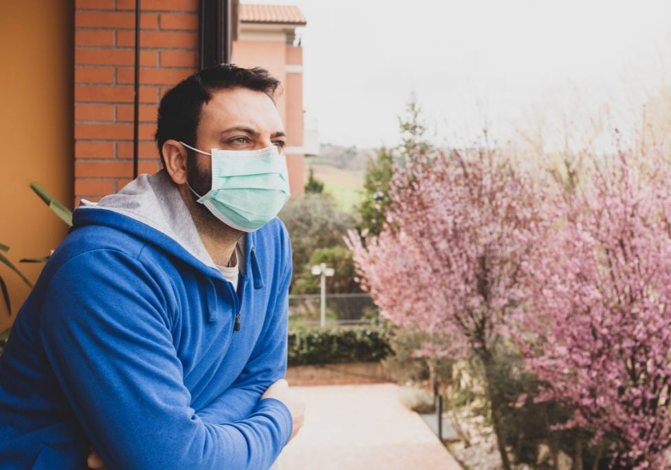 Young caucasian man with mask looking out on the terrace of the house during the quarantine due to the pandemic of covid19 coronavirus.